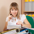 Stock Photo: Businesswoman reading documents in office