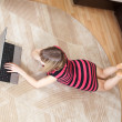 Stock Photo: Girl lying on floor and using laptop