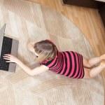 Girl lying on floor and using laptop — Stock Photo