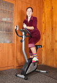 Woman exercising on exercise bike — Stock Photo