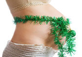 Pregnant belly with christmas decorations — Stock Photo
