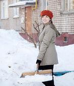 Flicka kastar snö med spade — Stockfoto