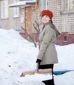 Girl throwing snow with shovel — Foto Stock