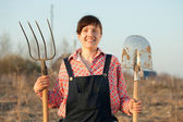 Happy farmer with spade and pitchfork — Stock Photo