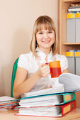 Businesswoman reading documents and drinking tea — Stock Photo