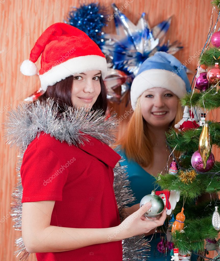 Girls in christmas hats near spruce at home — Stock Photo #8135215