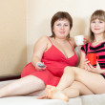 Women looking TV and drinking tea — Stock Photo