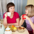 Foto Stock: Two girls gossiping and drinking tea