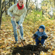 Family planting tree r in autumn - Stock Photo