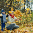 Mother with   boy  throwing maple leaves - Stock Photo