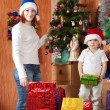 Foto Stock: Woman with son near decoration spruce