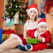 Woman and boy dressed like Santa Claus - Stok fotoğraf