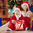 Boy dressed like Santa Claus with mother - Stok fotoğraf