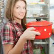 Girl putting pan into refrigerator — Stockfoto