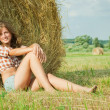Girl  resting on straw bale - Stock Photo