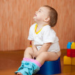 Happy toddler sitting on potty - Stock Photo