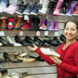 Mature woman chooses shoes — Stock Photo