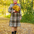 Elderly woman  walking in autumn park - Stock Photo