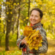 Mature woman against autumn landscape - Stock Photo