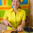 Foto Stock: Womslicing prune on cutting board
