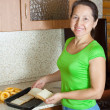 Woman puts toast bread into roasting tray - ストック写真