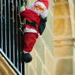 Santa Claus climbing up house - Stock Photo