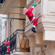 Santa Claus climbing up house - Stok fotoğraf