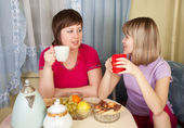 Two girls gossiping and drinking tea — Stock Photo
