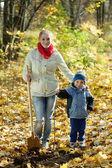 Mujer con su hijo hacer huerta en otoño — Foto de Stock