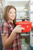 Girl putting pan into refrigerator — Stock Photo