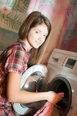 Chica poner ropa en la lavadora — Foto de Stock