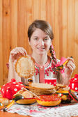 Girl in traditional clothes eating pancake — Stock Photo
