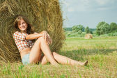 Girl resting on straw bale — Stock Photo
