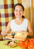 Woman adds grated eggs and sliced olives in mincemeat — Stock Photo