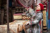 Mature woman chooses carpet — Stock Photo