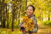 Mature woman against autumn landscape — Stock Photo
