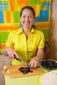 Woman slicing prune on cutting board — Stock Photo