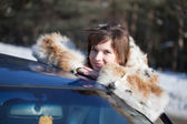 Woman near her car in winter road — Stock Photo