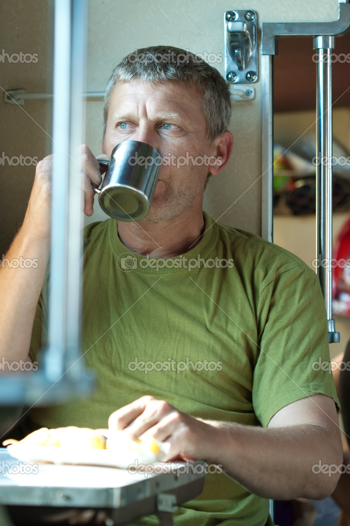 Middle-aged man drinks tea  in sleeper train — Stock Photo #8140100