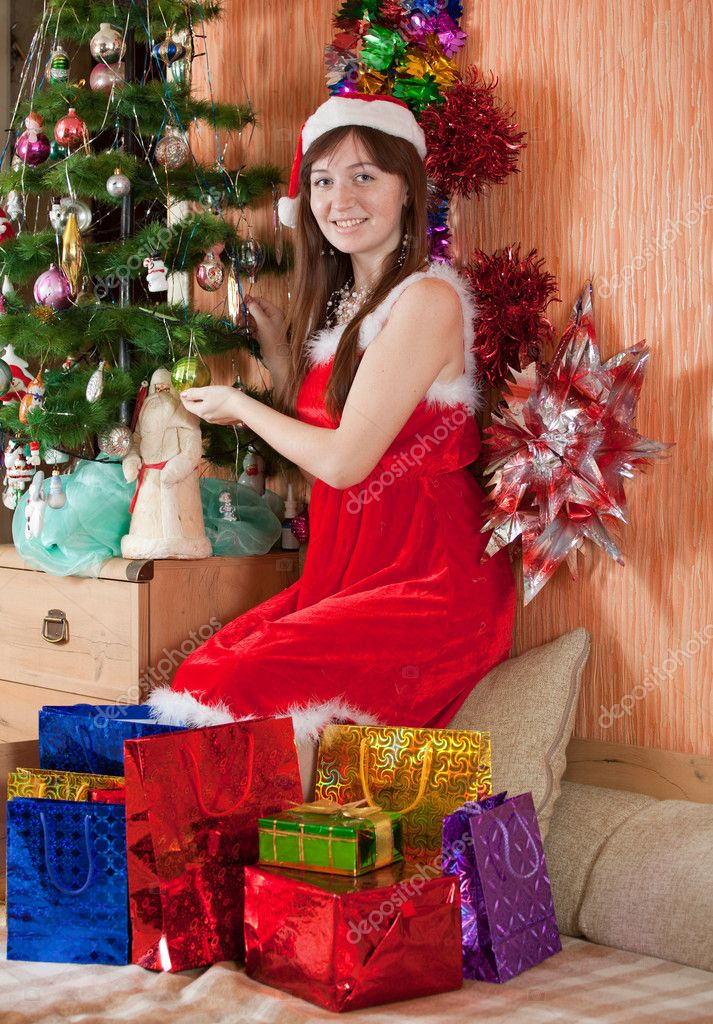 Girl in Santa hat sits with christmas presents  Foto de Stock   #8998904
