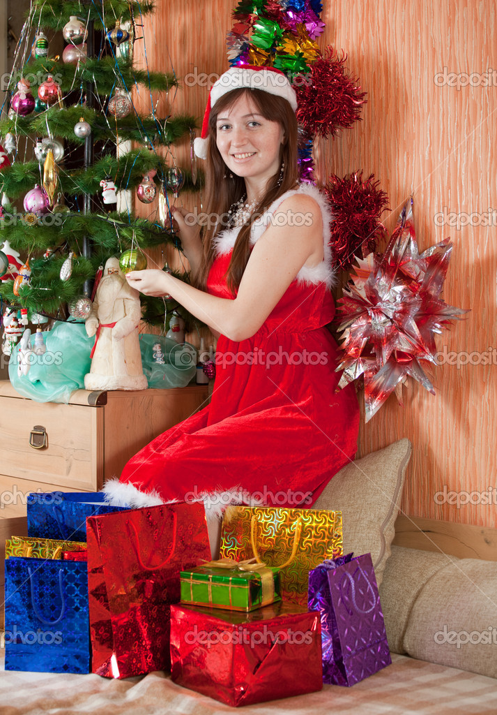 Girl in Santa hat sits with christmas presents   #8998904