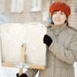Woman with shovel in winter - Stock Photo