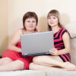 Girls on sofa with laptop — Stock Photo