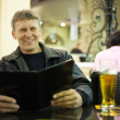 Mature man reading menu card - Stock Photo