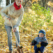 Woman with   son setting tree in autumn - Stockfoto
