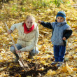Woman with  son resetting  tree in autumn - Stockfoto