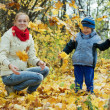 Foto Stock: Happy mother with boy throw up maple