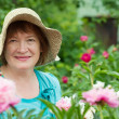 Foto Stock: Happy mature womwith peony plant