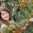 Stock Photo: Woman in seabuckthorn plant
