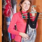 Girl chooses dress in wardrobe — Stock Photo